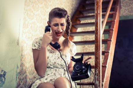 mujer llorando: Mujer sentada en las escaleras y gritando en el teléfono