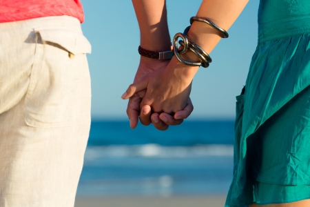 couple holding hands: Man and woman couple enjoying the romantic sunset on a beach by the ocean in their vacation, they standing hand in hand, closeup Stock Photo