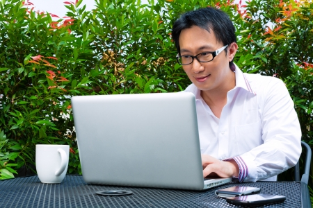 conductive: Asian Businessman working outdoor - he is working with laptop and checking emails Stock Photo