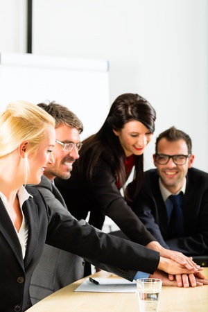joining the team: Business - businesspeople have team meeting or workshop in an office and joining hands, it is a very good team Stock Photo