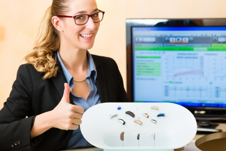 Young Woman or hearing accoustician holding a selection of hearing aids photo