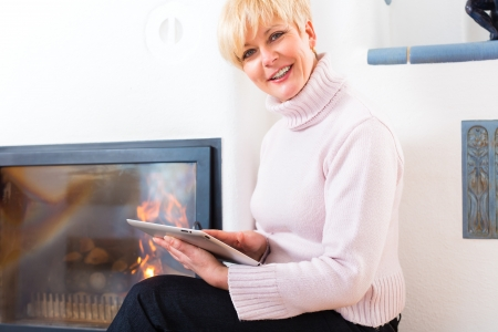 Quality of life - Older Woman or female Pensioner sitting at home in front of the furnace, writing emails on the tablet computer or reading a e-book Stock Photo - 20757304
