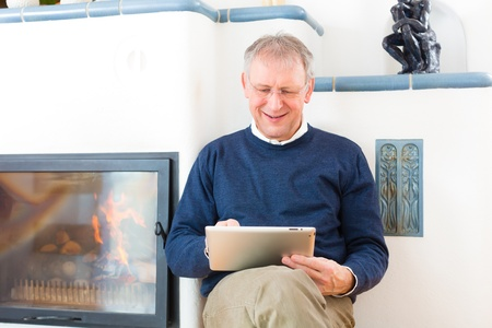Quality of life - Older man or Pensioner sitting at home in front of the furnace, writing emails on the tablet computer or reading a e-book Stock Photo - 20757305