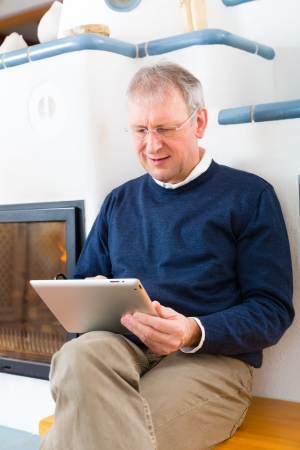 communicative: Quality of life - Older man or Pensioner sitting at home in front of the furnace, writing emails on the tablet computer or reading a e-book Stock Photo