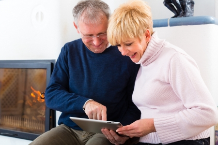 quality home: Quality of life - two elderly people sitting at home in front of the furnace, writing emails on the tablet computer