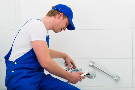 bluey: Emergency Service - Plumber or contractor repairing a not working shower in the bath Stock Photo
