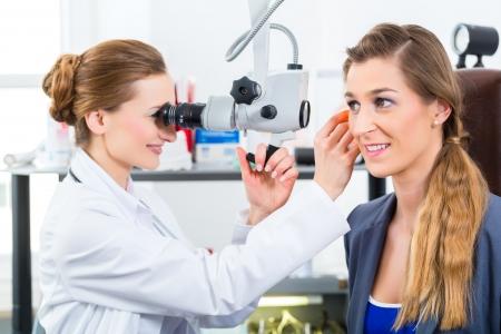 Doctor - Junge weibliche Arzt oder HNO-Arzt - mit einem Patienten in ihrer Praxis, die Pr�fung des Ohres mit einem Endoskop Lizenzfreie Bilder