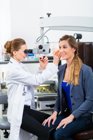 endoscope: Doctor - Young female doctor or ENT specialist - with a patient in her practice, examining the ear with a endoscope