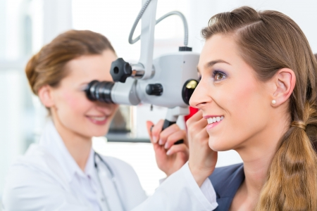 ent: Doctor - Young female doctor or ENT specialist - with a patient in her practice, examining the ear with a endoscope