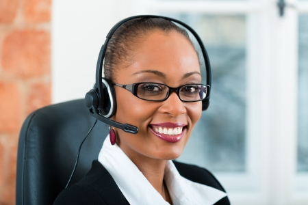 legal services: Young businesswoman or secretary working in her Office with a headset, she has a customer pitch Stock Photo