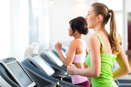 Running on treadmill in gym or fitness club - two women exercising to gain more fitness Stock Photo