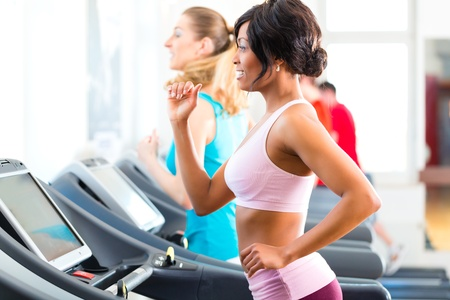 Running on treadmill in gym or fitness club - two women exercising to gain more fitness photo