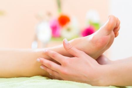 massage pied: Femme dans un salon de manucure recevoir une p�dicure par une esth�ticienne, elle devient un massage des pieds Banque d'images