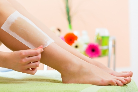 waxed legs: Young woman in Spa getting legs waxed for hair removal