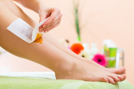 sugaring: Young woman in Spa getting legs waxed for hair removal