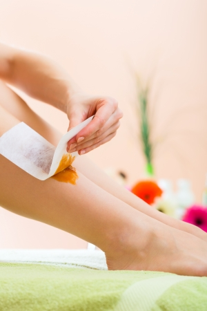 day spa: Young woman in Spa getting legs waxed for hair removal