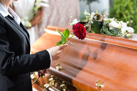 casket: Mourning woman on funeral with red rose standing at casket or coffin