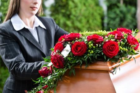 Mujer de luto en el funeral con una rosa roja de pie en ata?d o f?retro
