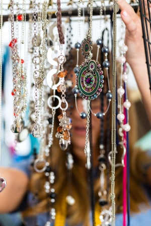 costume jewelry: Freelance - jewelry designer working on a draft, different pieces of jewelry hanging in front Stock Photo