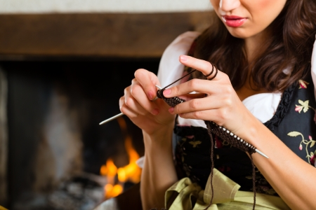trachten: Young woman in a traditional mountain hut with fireplace knitting Stock Photo