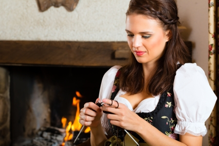 Young woman in a traditional mountain hut with fireplace knitting Stock Photo - 20836805