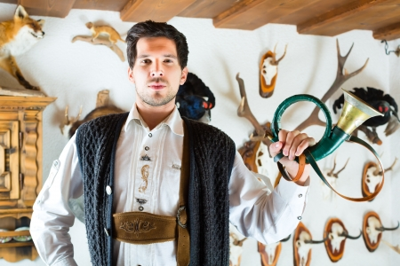 hunter's cabin: Young hunter with a bugle in front of a Wall with different horns, antlers and trophies in an alpine cabin Stock Photo