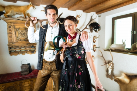 Young hunter with his wife and a bugle in front of a Wall with different horns, antlers and trophies in an alpine cabin Stock Photo - 20836808