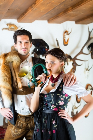 Young hunter with his wife and a bugle in front of a Wall with different horns, antlers and trophies in an alpine cabin Stock Photo - 20836809