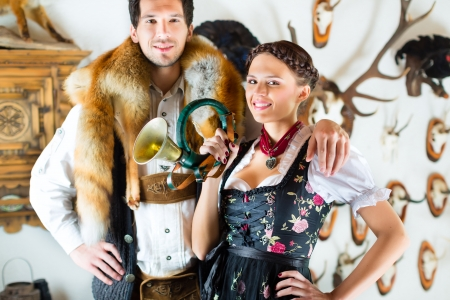 trachten: Young hunter with his wife and a bugle in front of a Wall with different horns, antlers and trophies in an alpine cabin Stock Photo
