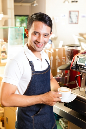 Coffeeshop - asian barista presents coffee in his shop photo