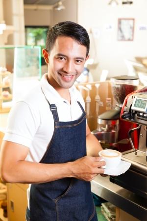 barista: Coffeeshop - asian barista presents coffee in his shop