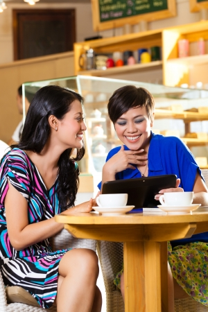 coffee shop: Asian female friends enjoying her leisure time in a cafe, drinking coffee or cappuccino and looking at photos or emails on a tablet computer