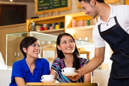 Aziatische vrouwelijke vrienden genieten van haar vrije tijd in een cafe, drinken cappuccino en praten over sommige dingen, een Indonesische ober serveert de koffie Stockfoto