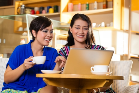 cafe shop: Asian female friends enjoying her leisure time in a cafe, drinking coffee or cappuccino and working on a laptop computer