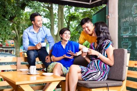 Aziatische vrienden of collega's genieten van vrije tijd in een cafe, drinken koffie of cappuccino en kijken naar foto's of e-mails op een tablet-computer