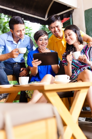 Asian friends or colleagues enjoying leisure time in a cafe, drinking coffee or cappuccino and looking at photos or emails on a tablet computer photo