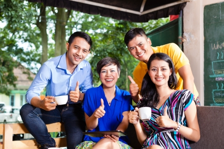 chinese drinks: Asian friends or colleagues enjoying leisure time in a cafe, drinking coffee or cappuccino and talking about some things