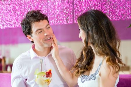 pareja comiendo: Pareja joven en un café o un helado salón, comiendo un helado juntos Foto de archivo