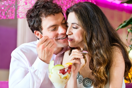 Young Couple in a Cafe or Ice cream parlor, eating an ice cream sundae together photo