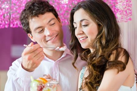 coppa di gelato: Giovane coppia in un bar o gelateria, mangiare un gelato sundae insieme