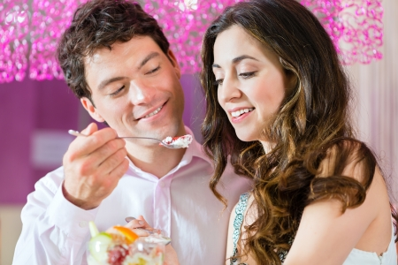 sundae: Young Couple in a Cafe or Ice cream parlor, eating an ice cream sundae together