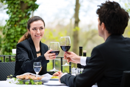 couple dining: Businesspeople having business lunch outside on the terrace in a fine dining restaurant