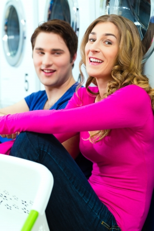 People in a launderette, washing their dirty laundry, sitting in front of washing machines and talking together photo