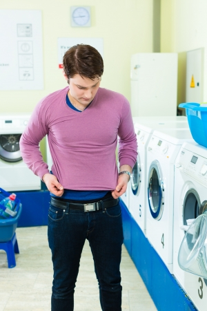 launderette: Young man in a launderette, washing his dirty laundry, in the background are washing machines, he is angry about his undersized top