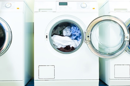 launderette: laundry with washing machines side by side, fresh laundry lies in the drum