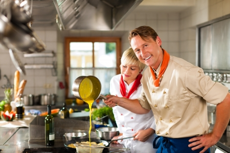 mujeres cocinando: Dos cocineros en el trabajo en equipo - hombre y mujer - en un hotel o restaurante cocina cocinar comida deliciosa