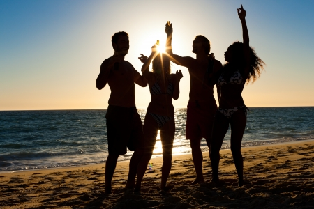 People (two couples) on the beach having a party, drinking and having a lot of fun in the sunset (only silhouette of people to be seen, people having bottles in their hands with the sun shining through) Stock Photo - 20932981