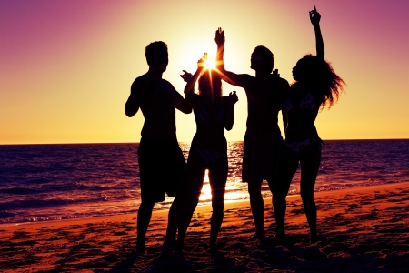 girl drinking: People (two couples) on the beach having a party, drinking and having a lot of fun in the sunset (only silhouette of people to be seen, people having bottles in their hands with the sun shining through)