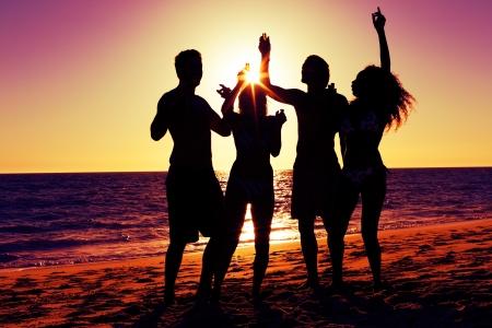 hombre tomando cerveza: Personas (dos parejas) en la playa de fiesta, beber y tener un mont?n de diversi?n en el sol (la silueta de las personas s?lo para ser visto, las personas que tienen las botellas en sus manos con el sol brillando a trav?s de) Foto de archivo