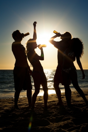 party silhouettes: People (two couples) on the beach having a party, drinking and having a lot of fun in the sunset (only silhouette of people to be seen, people having bottles in their hands with the sun shining through)